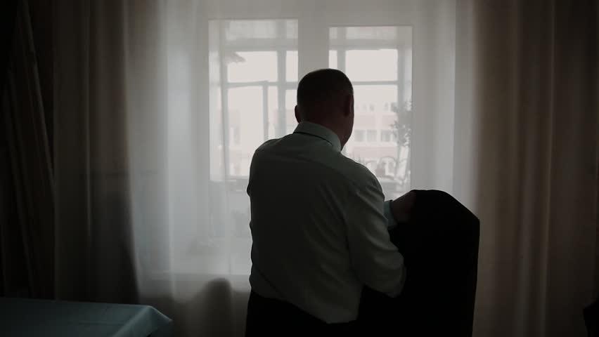 Man puts on black jacket standing before window. | Shutterstock HD Video #1025538407