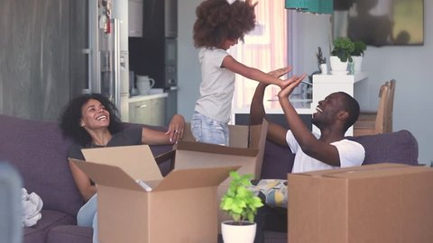 Happy child girl jump out of box give high five to dad play with black parents in living room, african family and kid daughter laughing having fun pack unpack enjoy relocation moving in new home