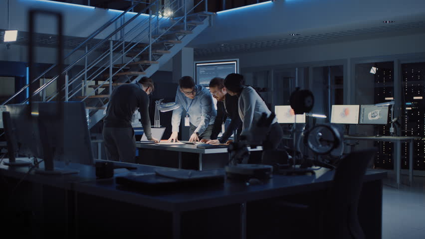 Diverse Team of Electronics Development Engineers Standing at the Desk Successfuly Solving Project Problems Late at Night, Celebrating with High Five and Cheers. Specialists Working on Design | Shutterstock HD Video #1025609567