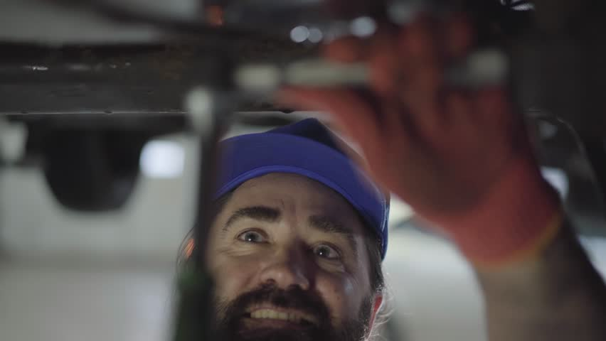 Professional bearded car mechanic screwing details of car with special tool on lifted automobile at repair service station close up. Skillful man in uniform fixing car. Car service, repair maintenance | Shutterstock HD Video #1025618717