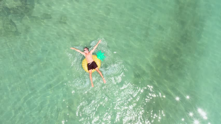 Drone point of view of young man relaxing on inflatable pineapple floating on sea. People travel beach holidays concept. Aerial view directly above of male enjoying freedom on tropical Islan vacations   Shutterstock HD Video #1025631977