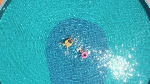 Drone view of young couple floating on swimming pool with inflatable mattresses enjoying their vacations in tropical paradise. Two people relaxing on holidays having fun in summer days sunbathing.
