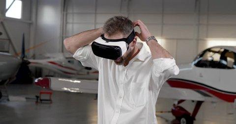 Caucasian aerospace engineer putting on virtual reality helmet standing in aircraft hangar