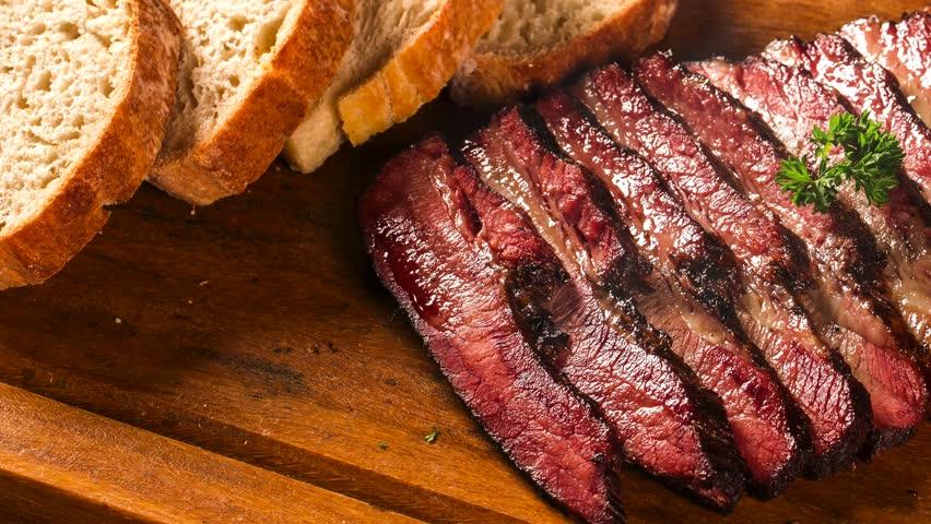 Slide shot Sliced brisket with bread. Smoke. | Shutterstock HD Video #1025696267
