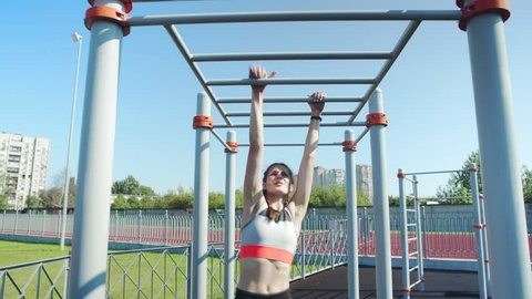Determined athletic girl in sports bra performing monkey bars climbing and resting to recover after it
