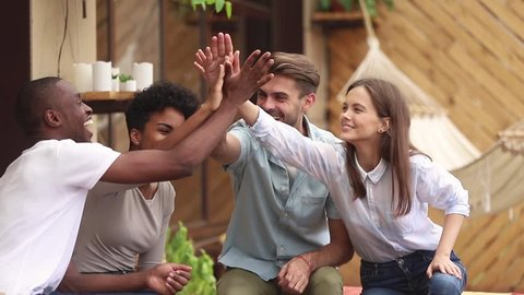 Happy diverse friends students group giving high five celebrating multi-ethnic friendship at meeting outdoor, young multicultural people join hands show unity support having fun making deal together