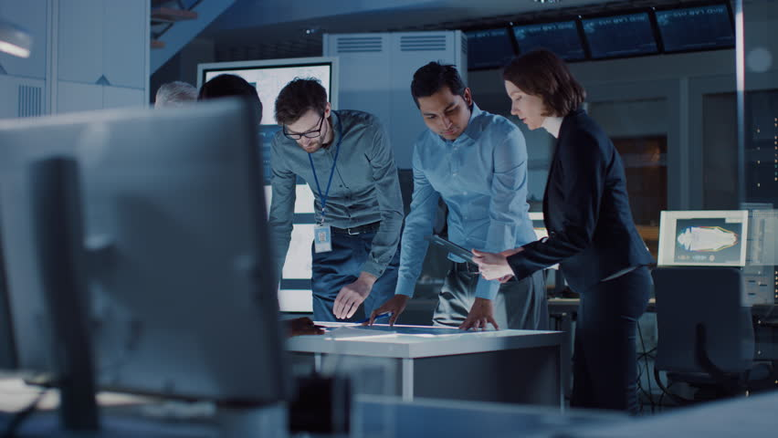 Engineers Meeting in Technology Research Laboratory: Engineers, Scientists and Developers Gathered Around Illuminated Conference Table, Talking and Finding Solution. Shot on 8K RED | Shutterstock HD Video #1025767427