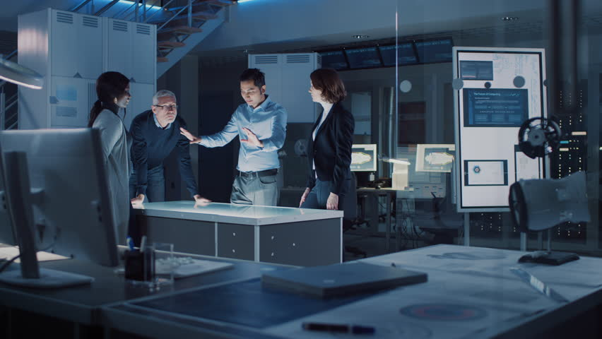 Engineers Meeting in Virtual Reality Content Design Studio: Engineers, Scientists and Game / Application Developers Gathered Around Illuminated Gesture Recognizing Conference Table.  Shot on 8K RED  | Shutterstock HD Video #1025767457