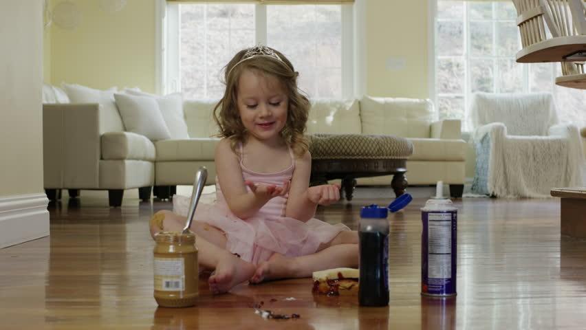 Medium shot of ballerina girl eating sandwich on floor