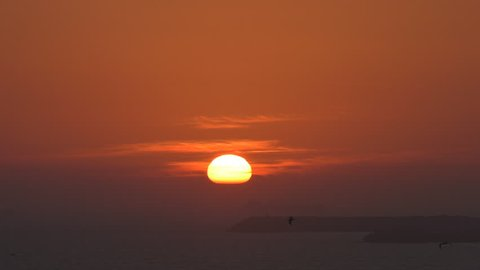 Sun is near sea horizon, birds flying in the red orange sky, big ship is hiding behind the breakwater barrier in the mist at sunset