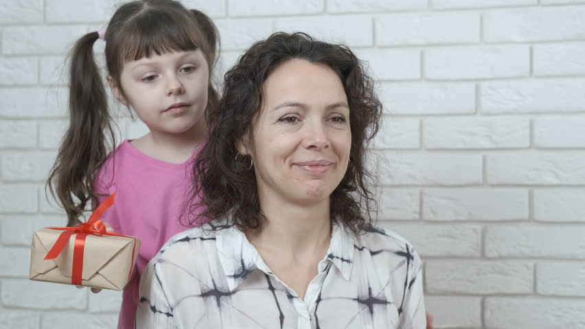 Mothers Day. The child closes the mother's eyes and gives a gift. | Shutterstock HD Video #1025828117