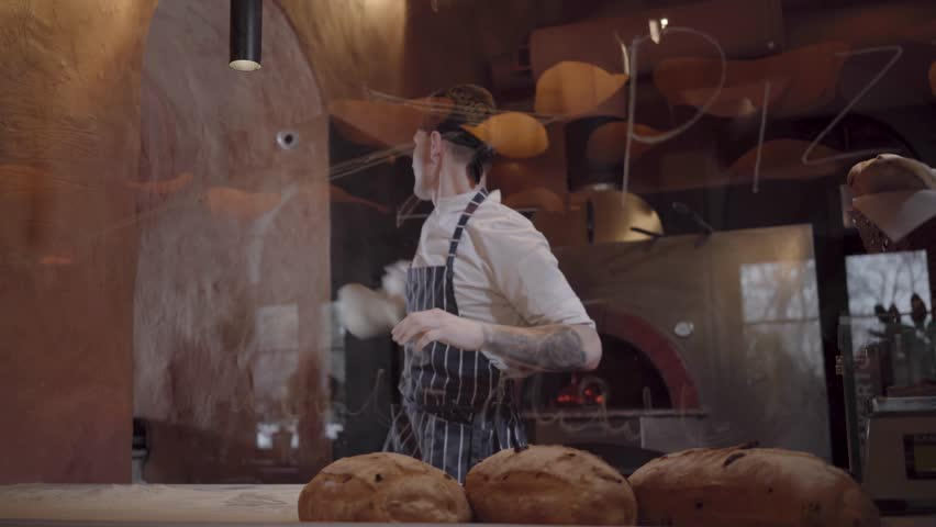 Young guy in chef uniform spinning and tossing pizza dough throwing it up behind glass in restaurant kitchen. Skillful young pizza maker is cooking dough at modern restaurant kitchen. Pizza cooking | Shutterstock HD Video #1025837237