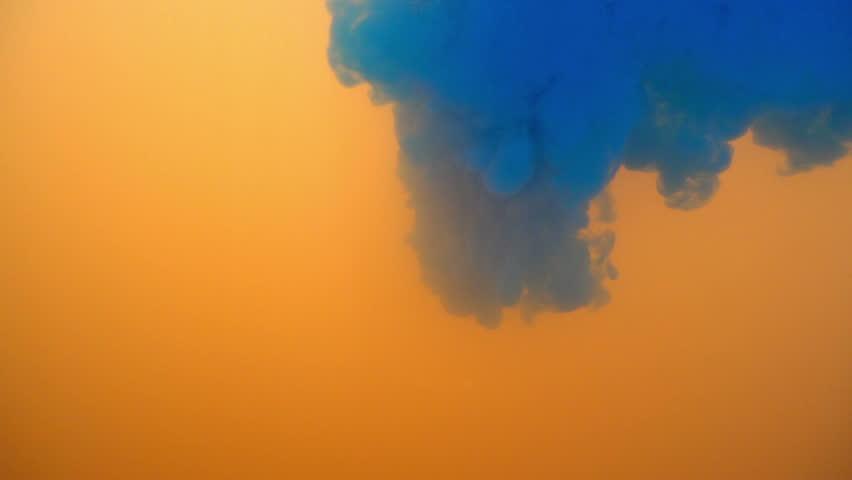 Blue color falling into orange background in slow motion.   Shutterstock HD Video #1025866667
