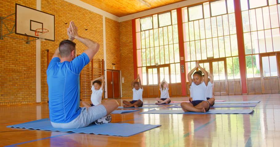 Rear view of yoga instructor teaching yoga to school kids in school. 4k | Shutterstock HD Video #1025908397