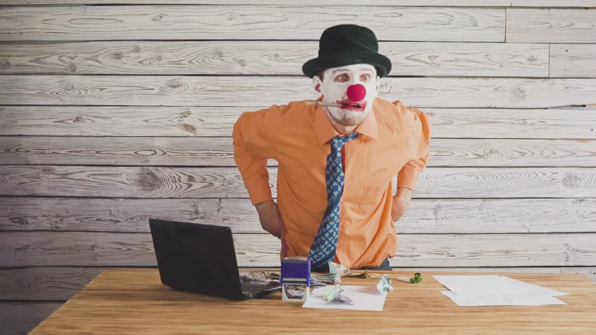 Clown businessman near the director's table swears at subordinates. Concept on angry stupid boss | Shutterstock HD Video #1025926667