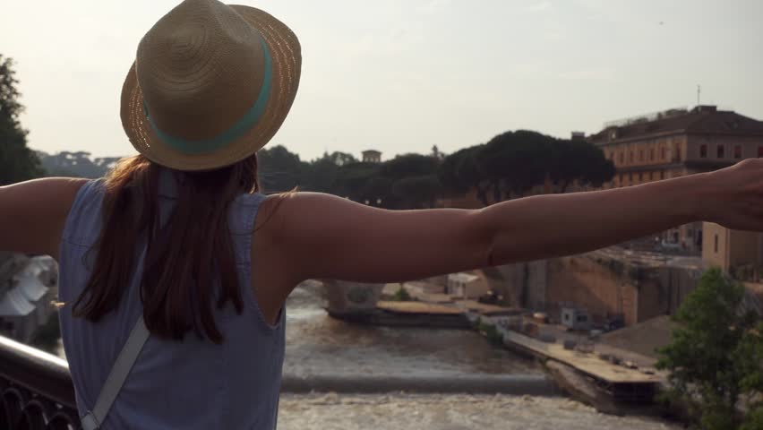 Back view of young woman in hat raising arms up in Rome, Italy. Happy female traveler outstretching hands in front of Tiber river. Slow motion of student traveling in european city. Concept of freedom | Shutterstock HD Video #1025939987