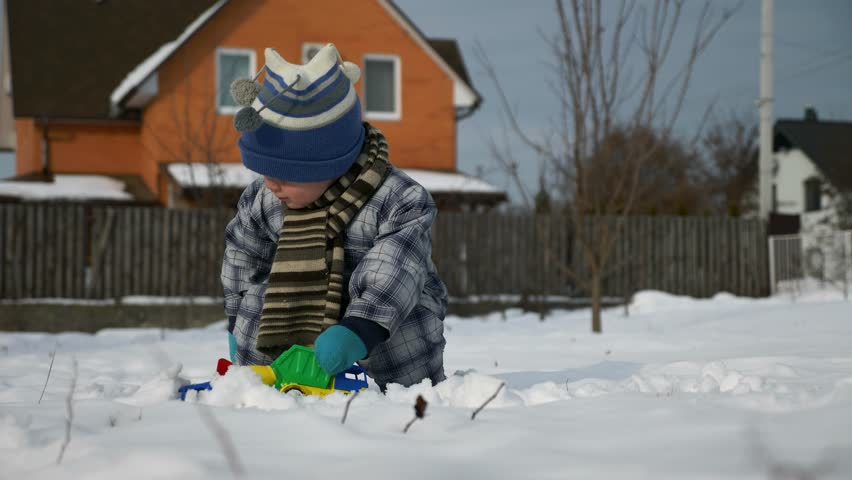 Little Boy Plays With Toy Trucks on Snow in Backyard Garden. Cold Weather on Winter Holidays. Bright Sunny Day. Slow motion 0.5 speed 60 fps | Shutterstock HD Video #1025946947
