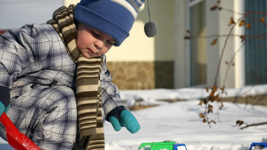 Little Boy Plays With Toy Trucks on Snow in Backyard Garden. Cold Weather on Winter Holidays. Bright Sunny Day. Slow motion 0.5 speed 60 fps | Shutterstock HD Video #1025946977