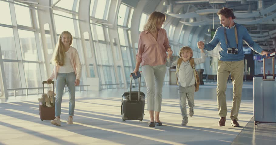 Caucasian happy mother, father, little daughter and son walking the airport hall and carrying their suitcases on the wheels before the departure to the vacation and laughing cheerfully  #1026000557