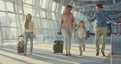 Caucasian happy mother, father, little daughter and son walking the airport hall and carrying their suitcases on the wheels before the departure to the vacation and laughing cheerfully