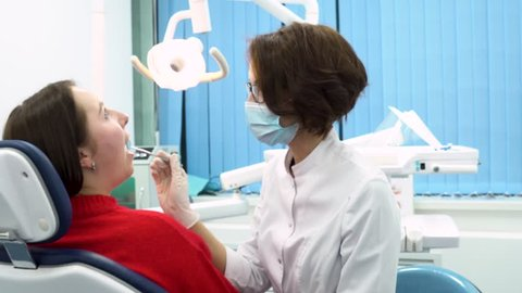 Girl dentist finishing to examine the oral cavity of the patient woman sitting in the dental chair, dental care concept. Young dentist in labcoat and a mask while treatment process.