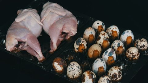 Fresh meat of quail in a plastic brown tray next to the quail eggs on a black background. Female hands put the eggs in the tray
