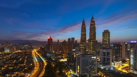 Aerial time lapse view of Kuala Lumpur city skyline with busy streets and expressway of  Malaysia at sunrise from twilight to day.