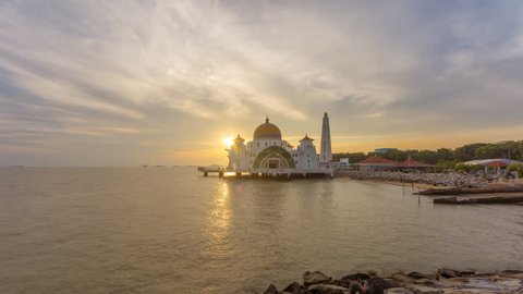 Time lapse on afternoon of scattered clouds at a floating Masjid Selat Melaka in Melaka, Malaysia. Pan down motion timelapse.