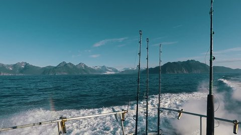 Back view of fishing boat with fishing rods and mountains in the background while sailing through the Gulf of Alaska