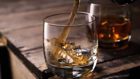 Golden whiskey pouring in the glass from the bottle. With ice cubes.