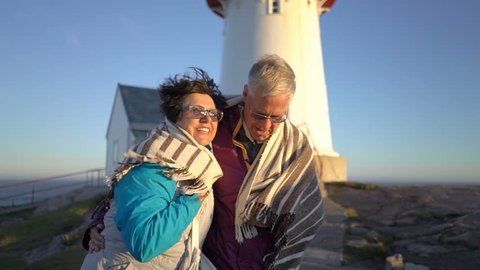 Mature couple walking at sunset on the seashore with an old lighthouse take care of each other, covering themselves with a plaid from the strong wind and hugging. Slow motion