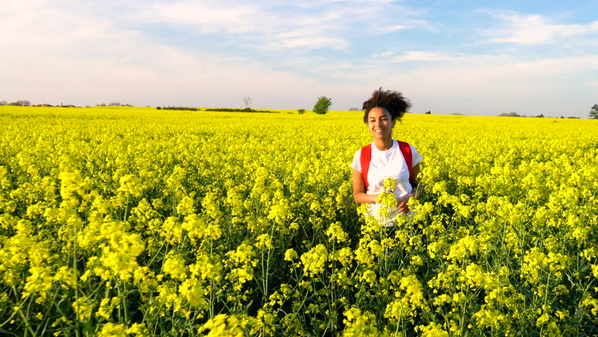 Beautiful happy mixed race African American girl teenager female young woman hiking with red backpack on path through field of yellow flowers. Stabilised tracking shot.
