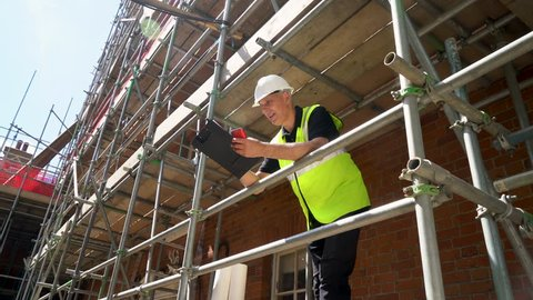 Male builder foreman, worker or architect working on construction building site standing on scaffolding writing on clipboard and talking on cell phone