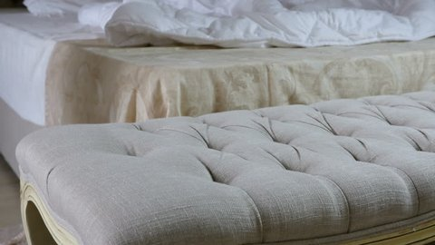 Woman throws erotic nightdress on a pouf before an unmade bed in a bedroom