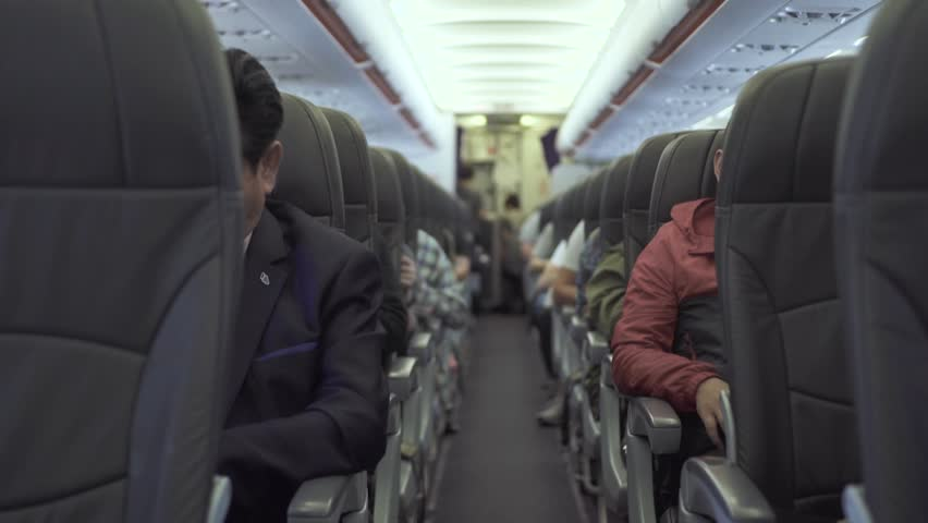 Passengers sitting on seats aircraft while flying in sky. Passengers inside cabin commercial plane while flight. Air traveling by modern commercial airplane   Shutterstock HD Video #1026153587