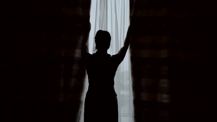 The female silhouette pushes back the curtains in the morning and stretches. Rear view. | Shutterstock HD Video #1026220877