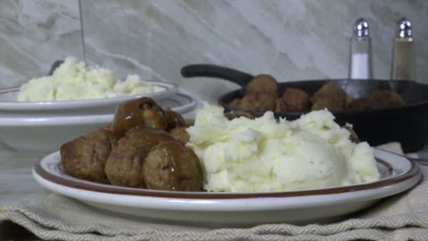 Pouring gravy over mashed potatoes and meatballs
