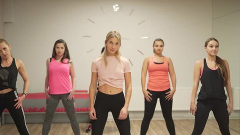 Young women in an aerobic class are doing synchronous exercises. Women is dancing in a fitness room and wearing sport clothes.