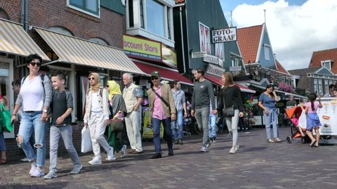 Volendam, Netherlands -August 18, 2018: Tourists walking near typical small Dutch houses with beautiful facades in Volendam. 4K