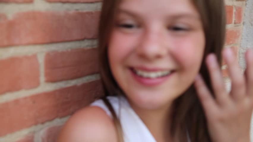 Teen girl portrait over a red brick wall. Selected focus. | Shutterstock HD Video #1026284747