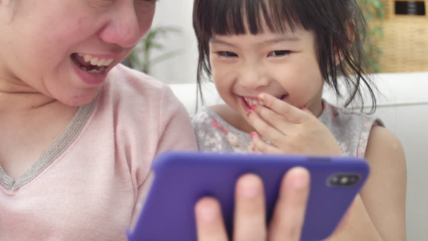 Happy asian family mother and daughter watching on phone and expand with smile face.  | Shutterstock HD Video #1026302267