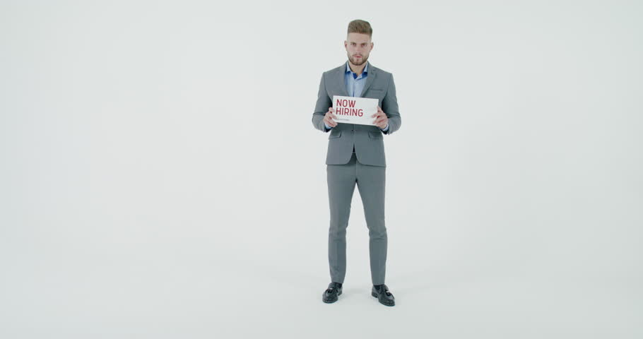 FIXED Handsome Caucasian HR manager wearing suit holding recruitment sign saying We are hiring. Light grey background. 4K UHD