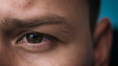 The human eye is depicted very closely with the brown (hazel) color of the movement of the eye and blink. Concept of: Hazel, Close to the eye, Man, Woman.