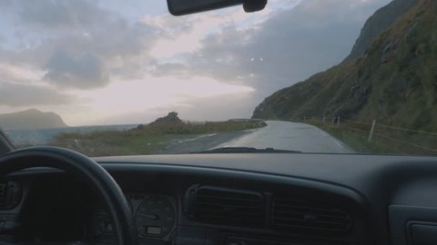Inside a car hands on a steering wheel driving on a road trip past beautiful mountains and a lake on a rainy overcast grey day in Norway