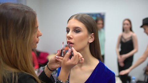 fashion show, visagist working, making professional make up, backstage. beautiful face of female girl model. Make up artist applying stylish makeup to young woman, visage for beauty contest
