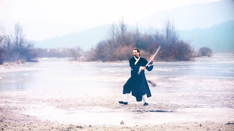 Sword play. Wide shot of man in kimono in focus training with katana. Surrounded by a frozen lake.