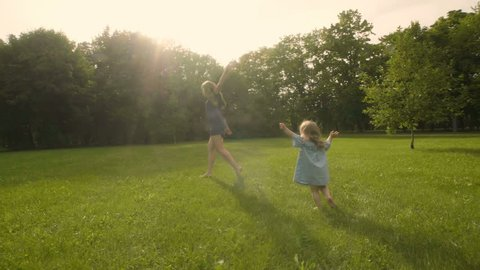 Baby girl with mother running through the grass in the summer sunlight in park. Baby have fun. Slow motion. Happy family concept. Child with mother running.