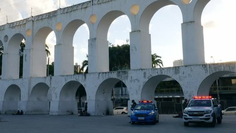 Rio de Janeiro, Brazil - March 26, 2019: Two police cars with officers keep vigil in front of the touristic 19th-century colonial Lapa Arches, Rio de Janeiro, Brazil