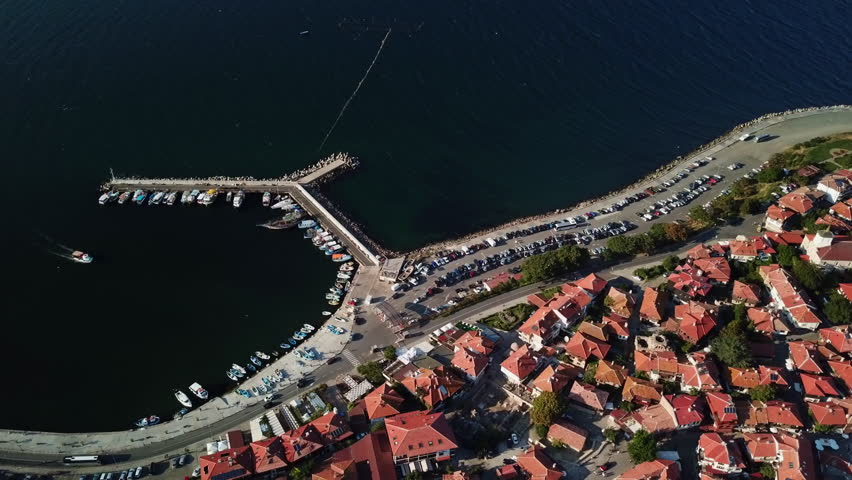 Flying over, aerial view of old Nessebar, ancient city on the Black Sea coast of Bulgaria, UNESCO World Heritage, marine and parking place