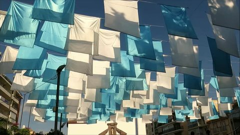 Blue and white flags blowing in wind above Fuengirola church square, Andalusia